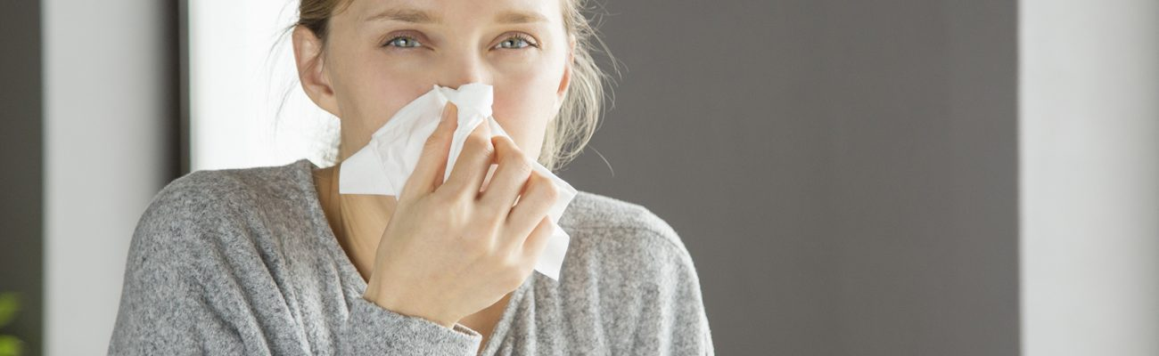 Pensive unhappy girl suffering from running nose. Young woman covering nose with tissue. Snuffle concept